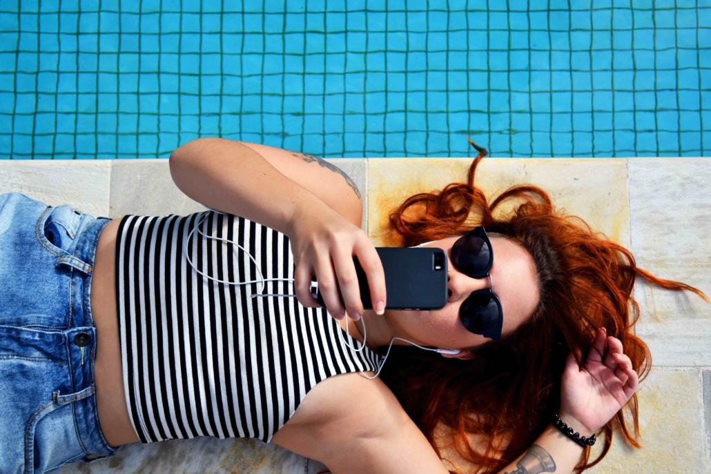 kvinna vid poolen kollar på sin mobil. Använder Instagram.