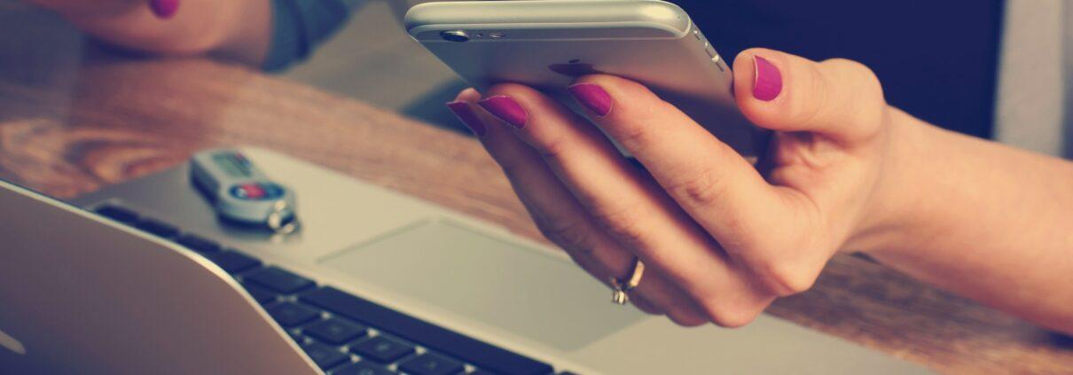 En kvinnlig hand som håller en mobil framför sin dator.