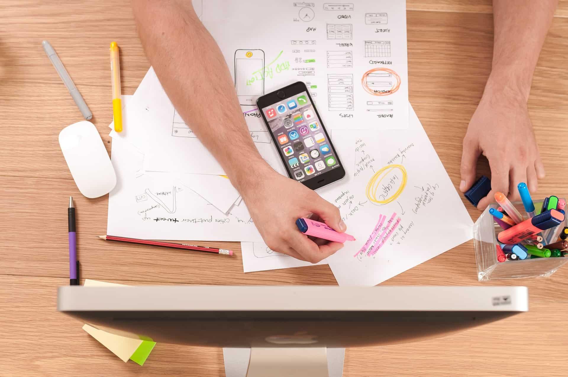 Ett bord fyllt av olika mobile user experience skisser och en mobil över pappren. En hand skissar på en av papprena.